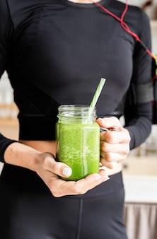 녹색 스무디 한 병을 들고 검은 운동복에 맞는 여자의 닫습니다