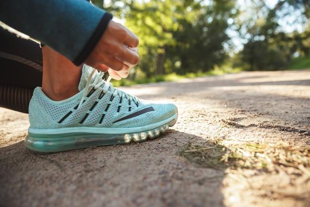 彼女の靴ひもを屋外で結ぶフィットネス女性のクローズアップ
