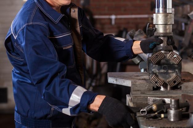 수리를 위해 자동 용접기에서 작업하는 파란색 유니폼에 배관공의 근접. 남자는 카르 단 샤프트 생산을 위해 공장에서 일합니다.