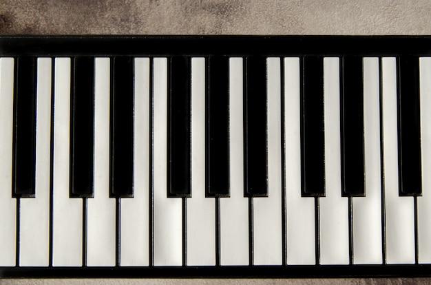 フラットピアノキーボードのクローズアップ、上面図。テクスチャードコンクリートの背景にピアノの鍵盤。テキスト用のスペース、コピースペース
