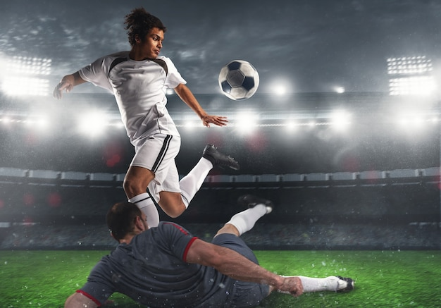 夜の試合中にスタジアムで競合するサッカー選手とサッカーのアクションシーンのクローズアップ