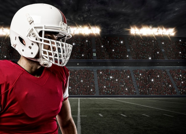 Закройте футболиста в красной форме на стадионе.