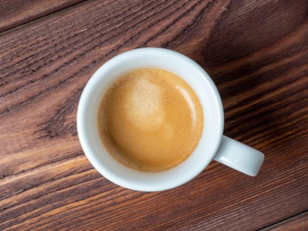 テクスチャード加工の木製の背景に白いカップの香りのよいコーヒーのクローズアップ。茶色のフォーム、上面図、フラットレイ