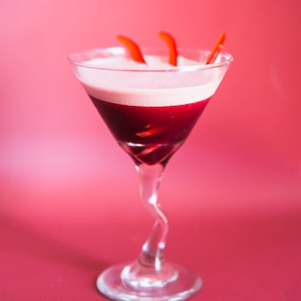 Close-up of a fresh cocktail in martini glass on pink background