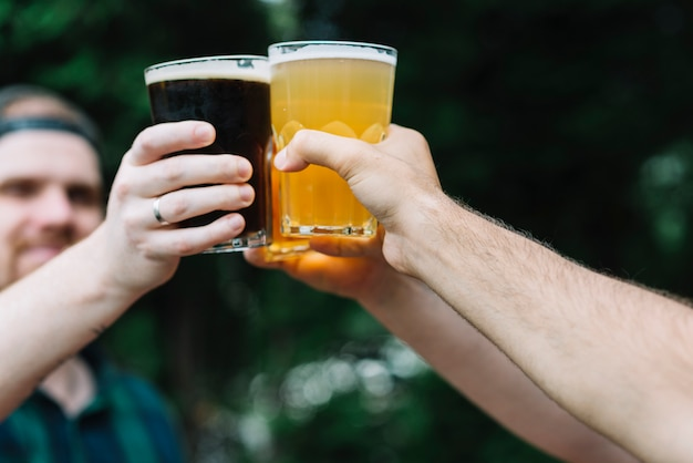 알코올 음료의 유리를 응원하는 친구의 손 클로즈업