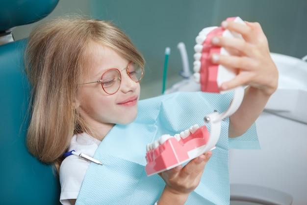 歯科医院で顎モデルを調べる面白い少女のクローズアップ