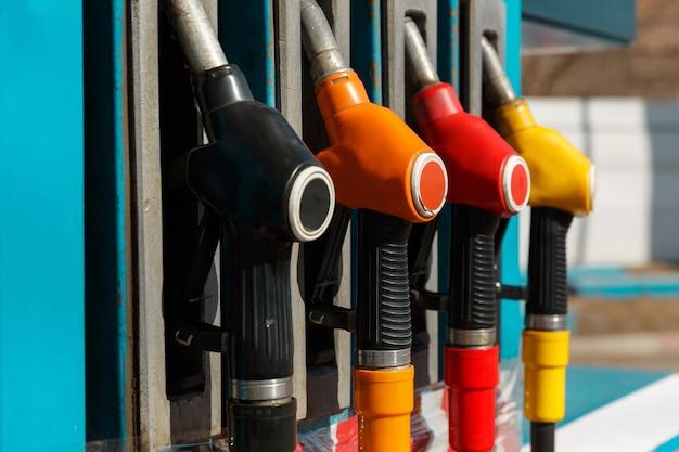 Крупный план заправочного пистолета для бензонасоса. бензозаправочная станция. сервисная азс с топливом, маслом, бензином и дизелем. вид сбоку. цвета черный, оранжевый, красный, желтый.