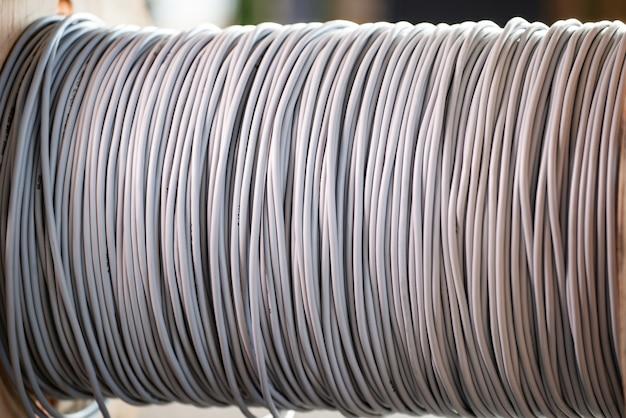 전기 장비 제조에서 나무 릴에 있는 거대한 회색 전선 타래의 클로즈업. 현대 기술 및 산업 볼륨의 개념