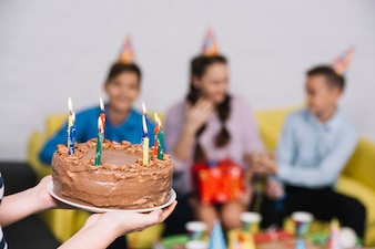 Close-up of a girl bringing chocolate cake decorated with lighted candles to her friends