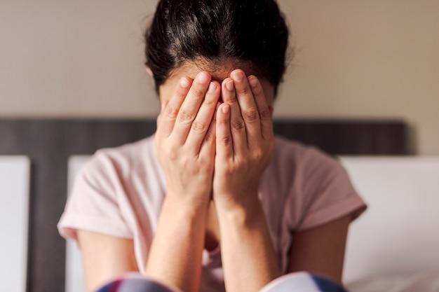 Крупным планом девушки плачут в своей комнате кровати