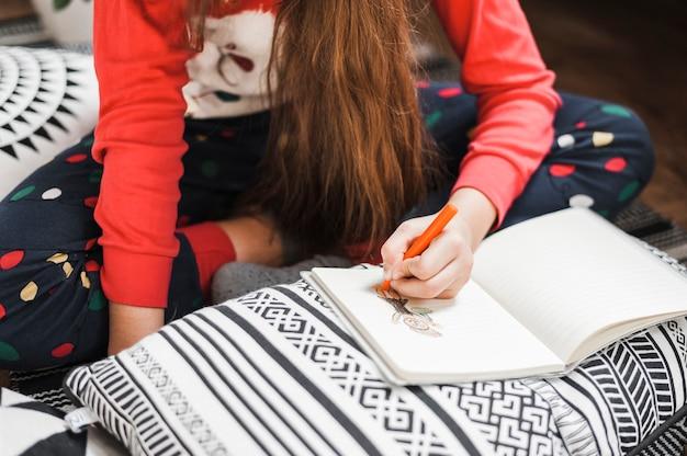 Крупный план девушки рисунок фигуры с карандаш на ноутбуке над подушкой