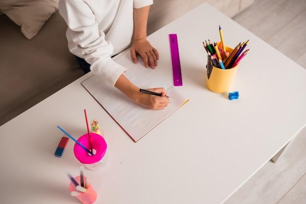 Крупный план девушки, рисующей в альбоме на столе