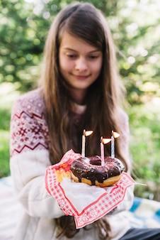 照明されたキャンドルとドーナツを保持する女の子のクローズアップ