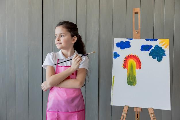 Крупным планом девушки с кистью в руке стоит возле мольберта, глядя в сторону