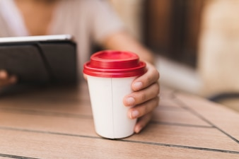 Close-up of a girl holding takeaway coffee cup on table