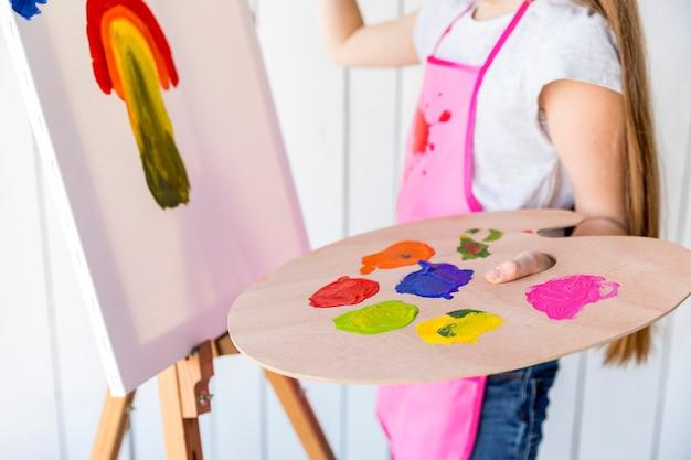 여러 가지 빛깔의 나무 팔레트를 손에 들고 캔버스에 여자 그림의 근접