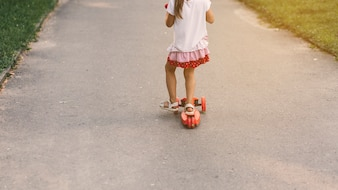 Close-up of a girl riding push scooter at street