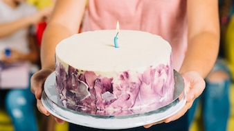 Close-up of a girl's hand holding birthday cake