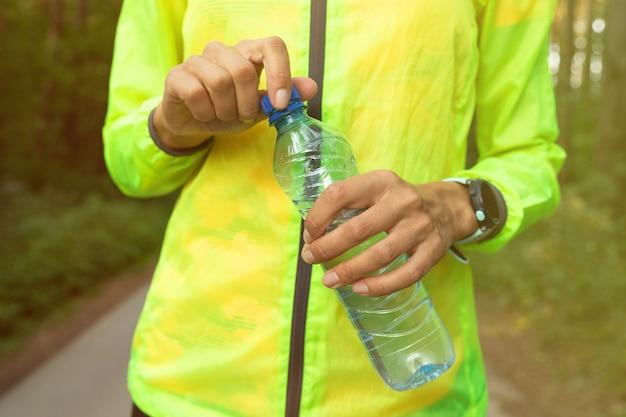 水のボトルを保持している明るい緑のウインドブレーカーで少女の手のクローズアップ