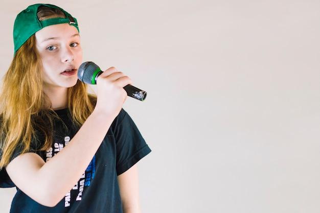 Крупный план девушка петь песню с микрофоном на цветном фоне