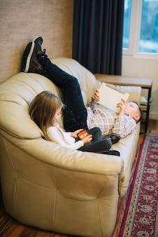 소파에 디지털 태블릿을보고 형제 근처에 앉아있는 여자의 근접