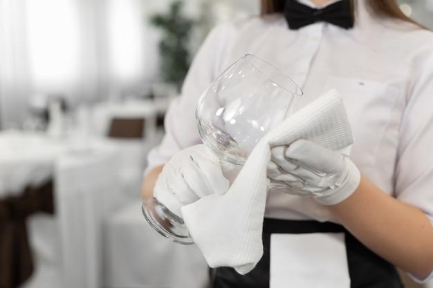 Крупный план стакана и полотенца в руках официанта. приготовление, сервировка стола.