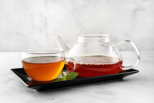 Крупным планом стеклянная чашка имбирного чая с чайником на черной тарелке и белом фоне