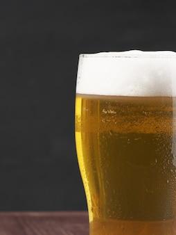 Крупный план стакана пены лагера. яркий освежающий алкогольный напиток