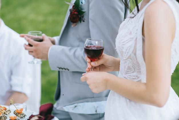屋外で白いドレスを着た花嫁の手に赤ワインのグラスのクローズアップ。背景にガラスを持った新郎の手。背景がぼやけている。