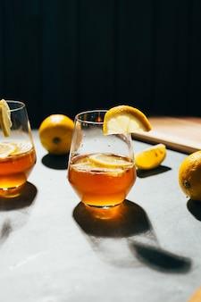 灰色の表面にレモンとグラスのアルコールカクテルとグラスのクローズアップ