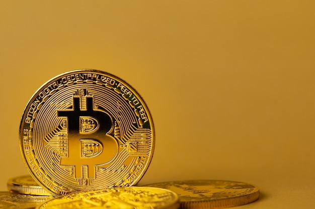 동전 더미에 있는 금 비트코인의 클로즈업. 가상 화폐 또는 블록체인 암호화폐. 개체가 왼쪽에 있는 큰 노란색 copyspace입니다.
