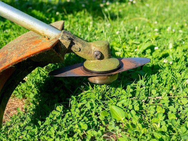 금속 칼 형태의 노즐이 있는 잔디 트리머의 클로즈업. 현장 유지 보수, 잔디 깎기