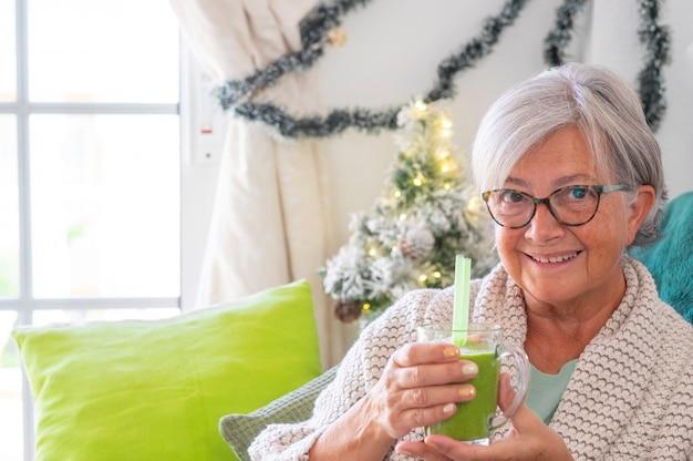 手に果物と野菜と自家製の緑のスムージーを保持しているカメラを見ながらソファに座って白髪の年配の女性のクローズアップ