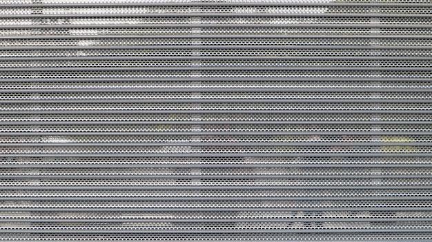 Крупным планом - серая металлическая сетка в качестве меры безопасности перед закрытым торговым центром. закрытые ворота на входе в магазин, препятствующие проникновению или уничтожению мест для преступников.