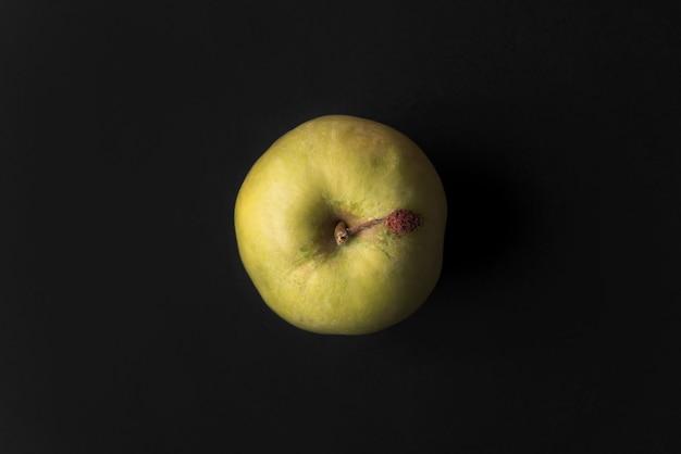 Близкое черное яблоко свежее изолированное над зеленым цветом вверх