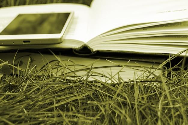 本と電話、教育の概念、学校に戻って緑の芝生の背景のクローズアップ。