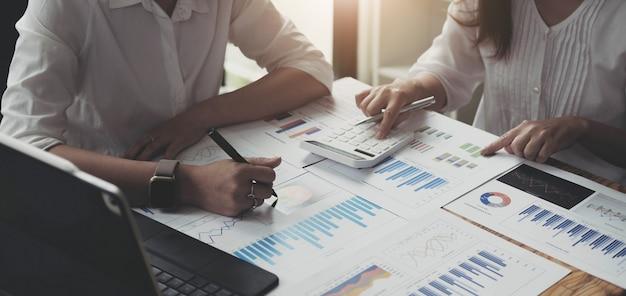 ブレーンストーミングをしているビジネスマンのグループのクローズアップは、オフィスで一緒に働いているリストを説明しています。