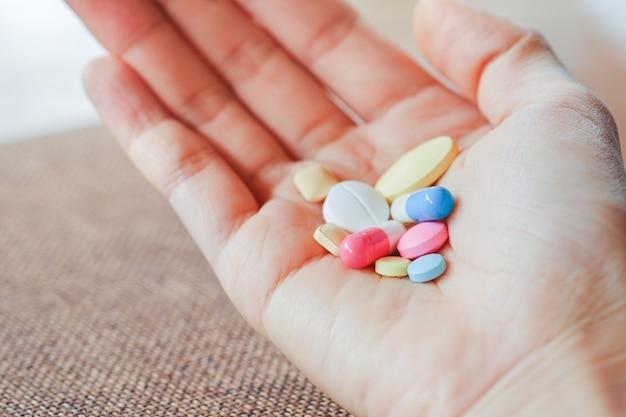Крупный план группы таблеток в руке женщины с размытым фоном. концепция здравоохранения.