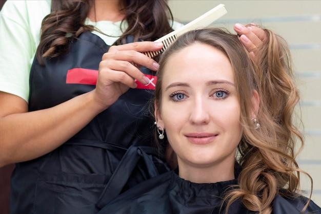 Крупным планом парикмахер делает прическу.