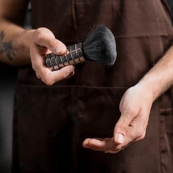 シェービングブラシを持っている美容師の手のクローズアップ