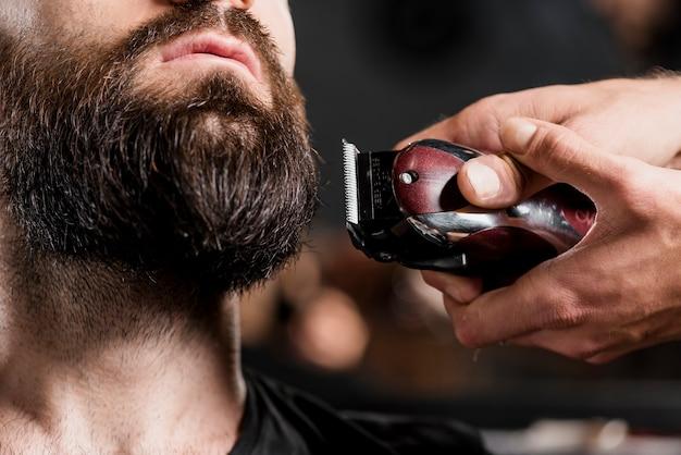 電気のトリマーで男性のひげをひげそりする美容師の手のクローズアップ