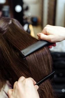 ヘアアイロンで長い茶色の髪を矯正する美容師のクローズアップ