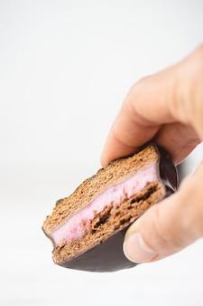 チョコレートを持っている手のクローズアップは、フィリングでクッキーをカバーしました。サンドイッチビスケット。
