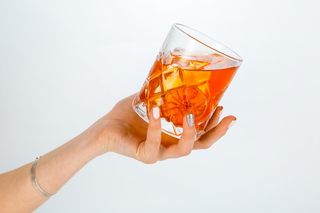 Закройте вверх руки держа стекло коктеиля negroni на белизне с космосом экземпляра.