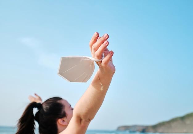 ビーチで保護マスクを持っている手のクローズアップ