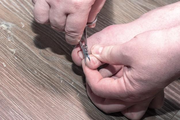 집에서 나무 배경에 발톱을 자르기 위해 가위를 들고 있는 손의 클로즈업. 건강한 손톱 개념입니다. 발톱 페디큐어. 손톱 손질. 문제가 있는 건강에 해로운 내성 발톱.