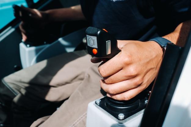 Крупный план руки, держащей ручку управления и готовой к работе в автокране, самом большом автокране для сложных задач.