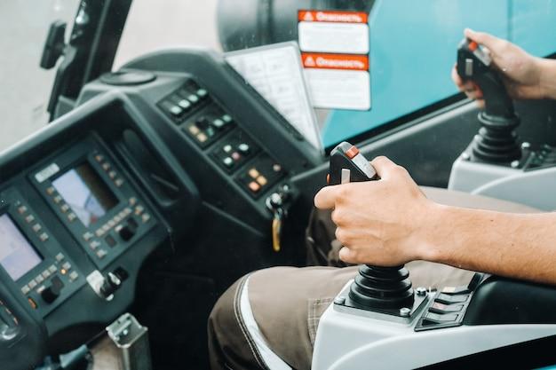 操縦桿を持っている手のクローズアップとトラッククレーンで作業する準備ができて挑戦的なタスクのための最大のトラッククレーン。
