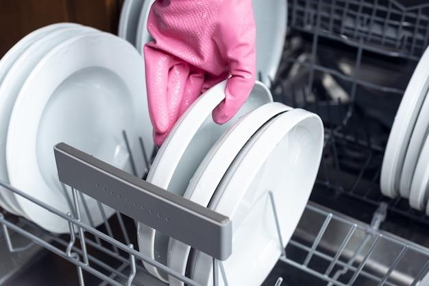 Крупным планом рука в розовой защитной перчатке кладет тарелку в посудомоечную машину