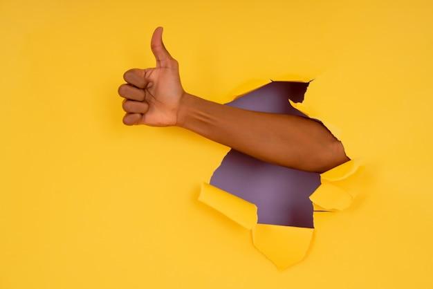 引き裂かれた紙の壁を介して手で親指を立てるジェスチャーを作る手のクローズアップ。